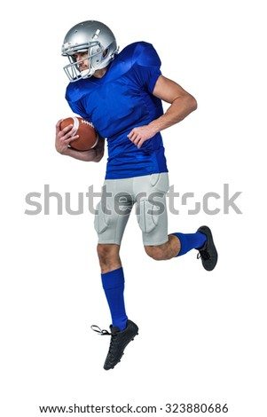 Full length of American football player holding ball in mid-air against white background