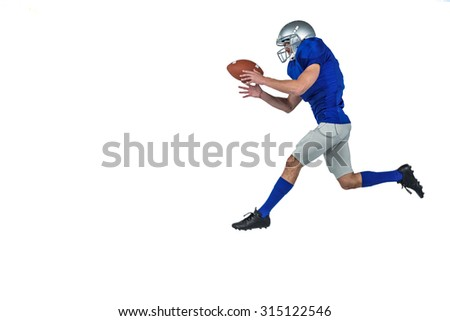 Full length of American football player running while catching ball against white background