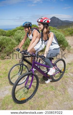 Full length of an athletic couple mountain biking - stock photo