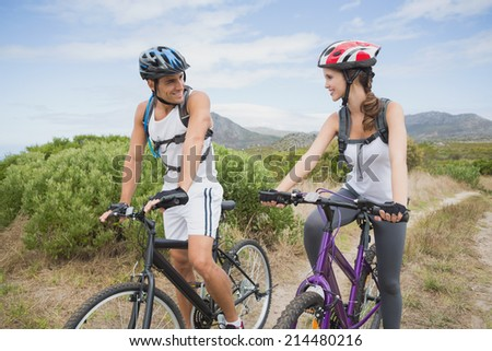 Full length of an athletic couple mountain biking