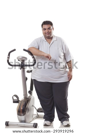 Full length of an obese man standing by an exercise bike over white background - stock photo