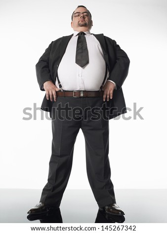 Full length of an overweight businessman standing with hands on hips against white background - stock photo