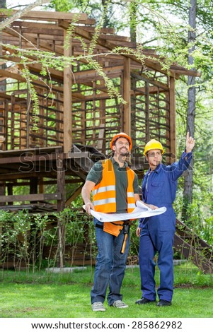 Full length of architects discussing over blueprint at construction site - stock photo