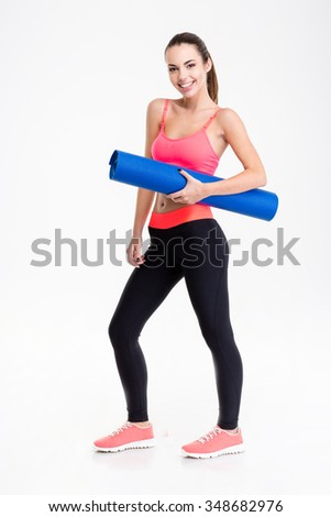 Full length of attractive smiling young fitness woman in sportwear holding yoga mat over white background - stock photo