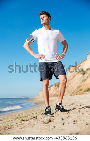 Full length of attractive young sportsman with cell phone standing on the beach - stock photo