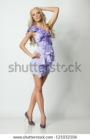 Full length of beautiful blond female standing in lilac dress over white background - stock photo