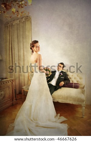 Full length of beautiful bride and groom in luxurious with vintage look interior and dress seen from the rear side - stock photo