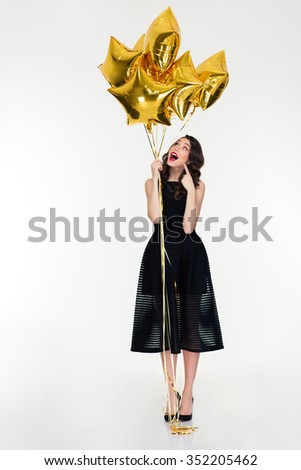 Full length of beautiful curious curly girl with bright makeup in retro style standing and pointing on golden balloons