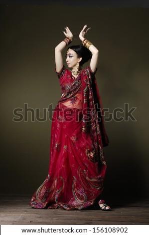 Full length of beautiful female wearing traditional indian costume posing in studio background
