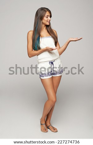 Full length of beautiful funky woman showing holding on the palm blank copy space, looking at palm, over gray background - stock photo