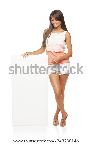 Full length of beautiful tanned woman in shorts standing leaning on white blank advertising board banner and pointing at it, over white background - stock photo