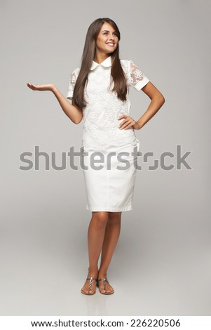 Full length of beautiful woman showing holding on the palm blank copy space over gray background - stock photo