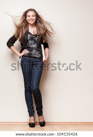 Full length of beautiful young girl standing near wall and holding laptop with both hands