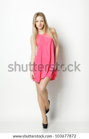 Full length of blond female in pink dress posing - stock photo