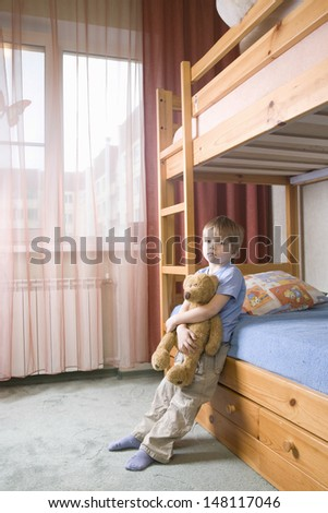 Full length of bored young boy with teddy bear leaning on bunk bed - stock photo
