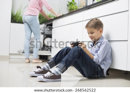 Full length of boy using hand-held video game with mother in background at kitchen - stock photo