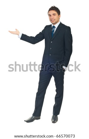 Full length of business man in black suit making presentation to copy space isolated on white background - stock photo