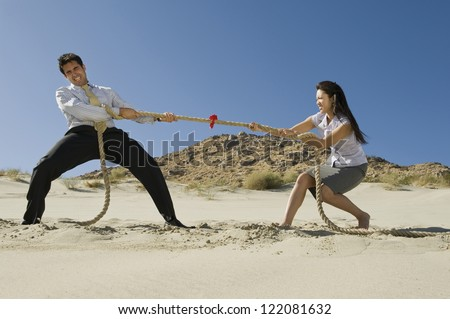 Full length of  business people playing tug of war in desert - stock photo