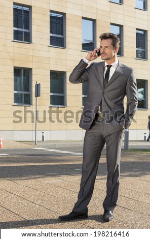 Full length of businessman conversing on cell phone against office building - stock photo