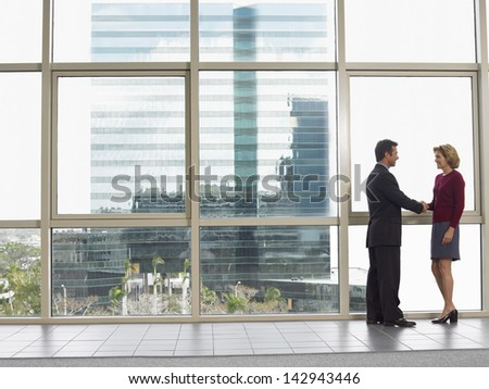 Full length of businessman shaking hands with female colleague in office building - stock photo