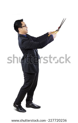 Full length of businessman using scissors to cut something, isolated on white background