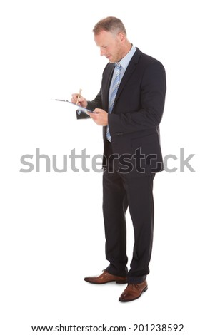 Full length of businessman writing on clipboard isolated over white background - stock photo