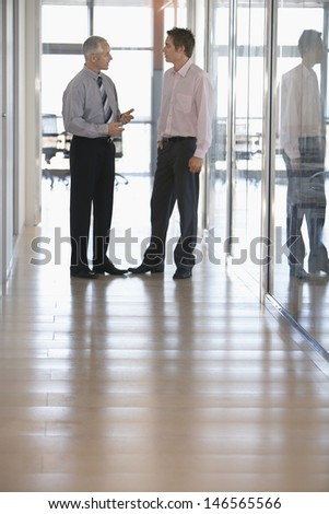 Full length of businessmen having a discussion in office corridor - stock photo