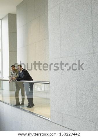 Full length of businessmen leaning on railing in office - stock photo