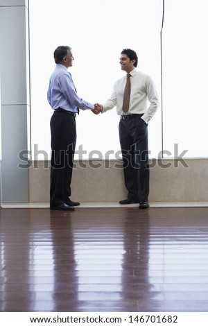 Full length of businessmen shaking hands in office - stock photo