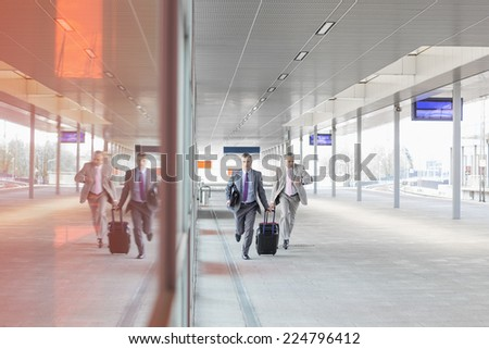 Full length of businessmen with luggage rushing on railroad platform - stock photo