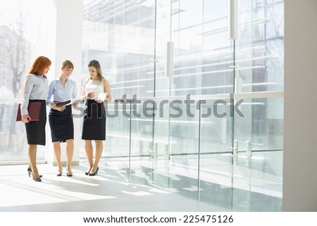Full-length of businesswomen doing paperwork in office - stock photo