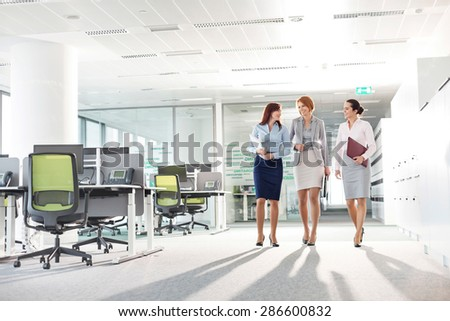 Full-length of businesswomen with file folders walking in office - stock photo