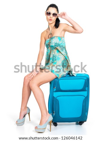 Full length of casual woman standing with travel suitcase - isolated on white background - stock photo