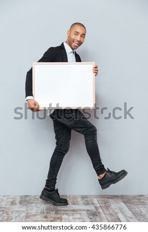 Full length of cheerful african young man walking and holding whiteboard - stock photo