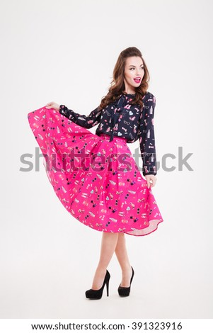 Full length of cheerful attractive young woman in bright pink skirt over white background - stock photo