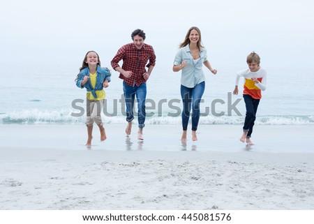 Full length of cheerful family running at beach against sky - stock photo