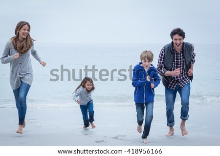 Full length of cheerful parents running at sea shore against sky - stock photo