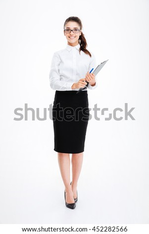 Full length of cheerful young business woman in glasses standing and holding clipboard over white background