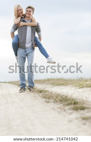 Full length of cheerful young man piggybacking woman on trail at field - stock photo