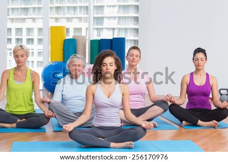Full length of class with female instructor in lotus position at gym - stock photo