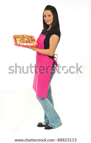 Full length of confectioner woman standing in semi profile and holding cakes isolated on white background - stock photo