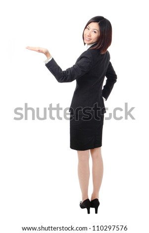 Full length of confident business woman showing something isolated over white background, view from back, model is a asian beauty - stock photo