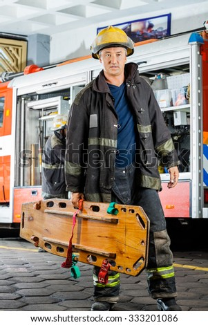 Full length of confident male firefighter carrying wooden stretcher against truck at fire station - stock photo