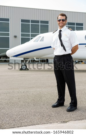 Full length of confident pilot with private jet in background - stock photo