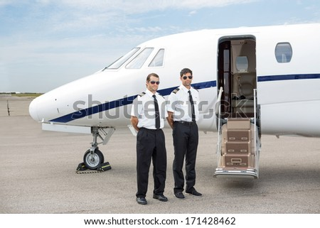 Full length of confident pilots standing in front of private jet with open door - stock photo