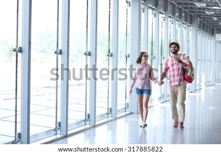 Full-length of couple holding hands while walking at covered passage - stock photo