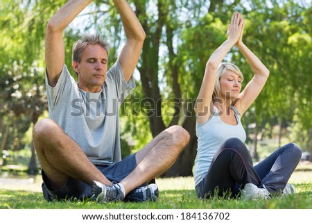 Full length of couple meditating with hands raised in the park