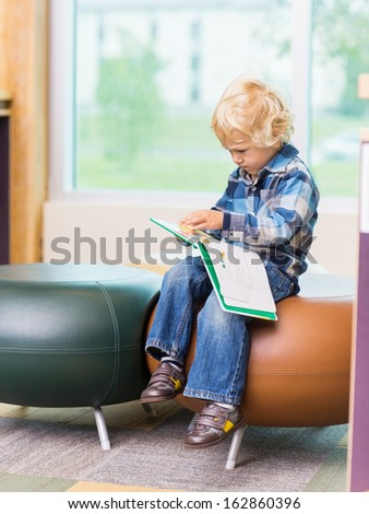 Full length of cute boy reading book on seat in school library - stock photo