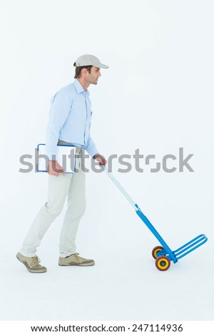Full length of delivery man pushing empty trolley over white background - stock photo