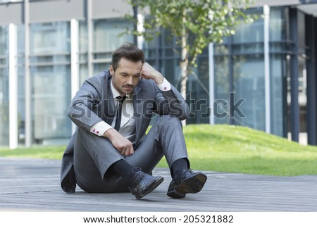 Full length of depressed businessman sitting on path outside office - stock photo